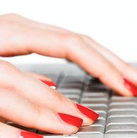 Red nails typing on computer keyboard